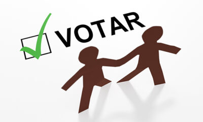 Two paper people of color with a Spanish votar checkbox and a green checkmark in a 3d illustration.